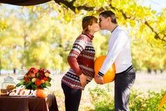 Pares embarazadas jovenes hermosos que tienen comida campestre en parque del otoño Ha Foto de archivo
