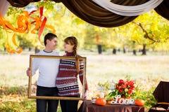 Pares embarazadas jovenes hermosos que tienen comida campestre en parque del otoño Ha Fotos de archivo libres de regalías