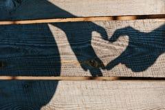Pares embarazadas que muestran el corazón de la sombra con los fingeres imagen de archivo libre de regalías