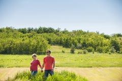 Pares embarazadas que se colocan delante de un campo y de una madera. Foto de archivo