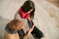 Pares embarazadas que se sientan en las escaleras Fotografía de archivo libre de regalías
