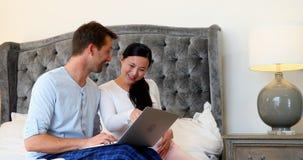 Pares embarazadas usando el ordenador portátil en cama en el dormitorio 4k almacen de metraje de vídeo