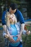 Pares embarazados de los jóvenes en parque Foto de archivo libre de regalías