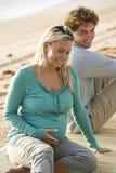 Pares embarazados de los jóvenes que se sientan en la estera en la playa Foto de archivo libre de regalías