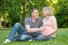 Pares embarazados en el parque Fotos de archivo libres de regalías