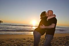 Pares embarazados en la playa en la puesta del sol fotografía de archivo libre de regalías