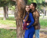 Pares embarazados felices Él la abraza de detrás Fotos de archivo libres de regalías