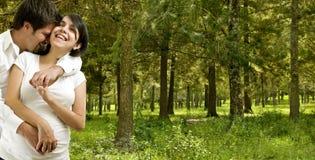 Pares embarazados felices casados jóvenes en bosque Imagenes de archivo