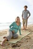 Pares embarazados jovenes felices en la arena en la playa Imágenes de archivo libres de regalías