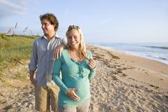 Pares embarazados jovenes felices que se colocan en la playa Imagen de archivo libre de regalías