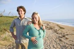 Pares embarazados jovenes felices que se colocan en la playa Fotos de archivo