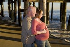 Pares embarazados que miran la puesta del sol fotos de archivo