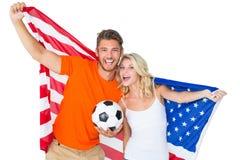 Pares emocionados del fanático del fútbol que sostienen la bandera de los E.E.U.U. Imagenes de archivo