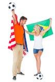 Pares emocionados del fanático del fútbol que sostienen los E.E.U.U. y la bandera de los brazils Imágenes de archivo libres de regalías