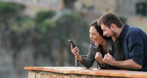 Pares emocionados que comprueban el contenido del teléfono en un balcón