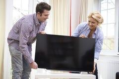 Pares emocionados que ponen la nueva televisión en casa Imagen de archivo