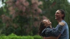 Pares emocionales de risa que abrazan y que se besan en la lluvia Dos amantes son muy felices de pasar el tiempo junto al aire li almacen de metraje de vídeo