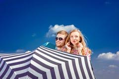 Pares emocionales que ocultan detrás del paraguas y que se divierten en el th Imagen de archivo libre de regalías