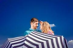Pares emocionales que ocultan detrás del paraguas y que se divierten en el th Imágenes de archivo libres de regalías