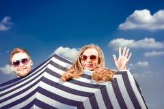 Pares emocionales que ocultan detrás del paraguas y que se divierten en el th Fotos de archivo libres de regalías