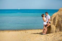 Pares en abrazos del amor en la playa cerca de la roca Fotografía de archivo