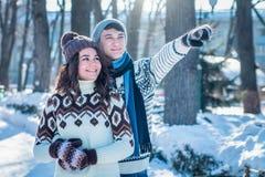 Pares en abrazos del amor en parque del invierno imagen de archivo