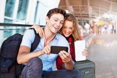 Pares en aeropuerto usando el viaje app foto de archivo