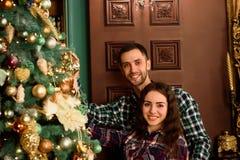 Pares en amor al lado de un árbol de navidad, abrazando y mirando a la cámara fotografía de archivo