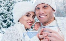Pares en amor con las tazas de té caliente en bosque del invierno de la nieve Imágenes de archivo libres de regalías