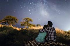 Pares en amor debajo de las estrellas de la galaxia de la vía láctea Fotografía de archivo