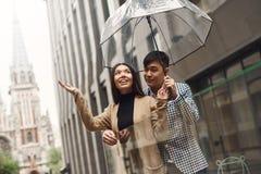 Pares en amor debajo del paraguas en el fondo de la alameda Fotos de archivo