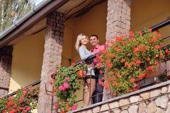 Pares en amor en el balcón entre las flores Fotografía de archivo