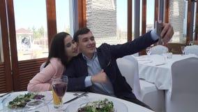 Pares en amor en el restaurante que hace el selfie en el vídeo de la cantidad de la acción del iPhone almacen de video