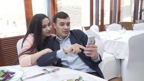 Pares en amor en el restaurante que hojea redes sociales en un vídeo de la cantidad de la acción del iPhone metrajes