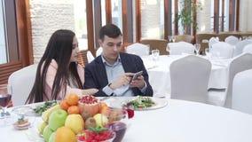 Pares en amor en el restaurante que hojea redes sociales en un vídeo de la cantidad de la acción del iPhone almacen de video