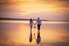 Pares en amor en la puesta del sol anaranjada del lago, wailking en agua Foto de archivo libre de regalías