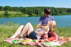 Pares en amor en una comida campestre en el lago Fotografía de archivo