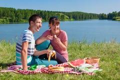Pares en amor en una comida campestre en el lago Imagen de archivo libre de regalías