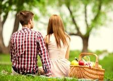 Pares en amor en una comida campestre en el parque, el día de tarjeta del día de San Valentín imagenes de archivo