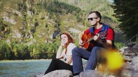 Pares en amor en la playa que toca la guitarra en un día de verano al lado del río de la montaña Fotos de archivo