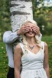 Pares en amor Ojos cubiertos hombre de la mujer rubia sonriente por sus manos en parque Foto de archivo libre de regalías