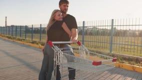 Pares en amor en un estacionamiento del supermercado con una carretilla de la tienda en la puesta del sol Cámara lenta metrajes