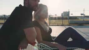 Pares en amor en un estacionamiento del supermercado con una carretilla de la tienda en la puesta del sol Cámara lenta almacen de video