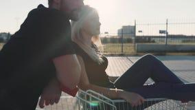 Pares en amor en un estacionamiento del supermercado con una carretilla de la tienda en la puesta del sol Cámara lenta almacen de metraje de vídeo