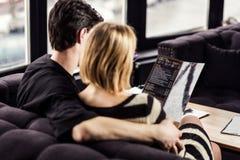 Pares en amor en un restaurante o un café que mira o que lee Fotografía de archivo