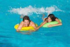 Pares en anillos inflables en la piscina Imagen de archivo libre de regalías