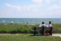 Pares en banco de la playa Imágenes de archivo libres de regalías