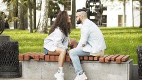 Pares en besarse del amor, sentándose en un banco en un parque que se mira almacen de metraje de vídeo