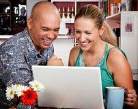 Pares en café con el ordenador portátil Foto de archivo libre de regalías