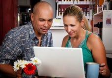 Pares en café con el ordenador portátil Fotografía de archivo libre de regalías